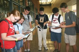 Amanda Grunder, Sara Lyon, Everett Thompson, Joseph Godfrey, Gage Lochner, and Kai Walberg look at the newly distributed yearbook Aug. 30.