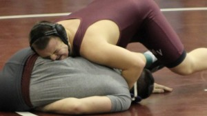 Senior Jacob Steele wrestles Coach Greg Murphy in front of a large crowd in the high school gymnasium, Jan. 30. Photo by Kelsey Shady.