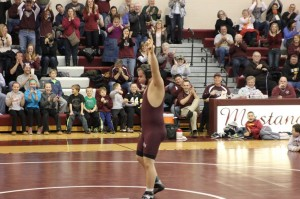 Jacob Steele celebrates his win on Senior Night as the crowd cheers. Photo by Kelsey Shady.