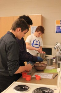 Sophomores Colin Heeren, Marquis Dew and Bryce Cox whip up a recipe in Foods in December. Photo by Laura Deininger.