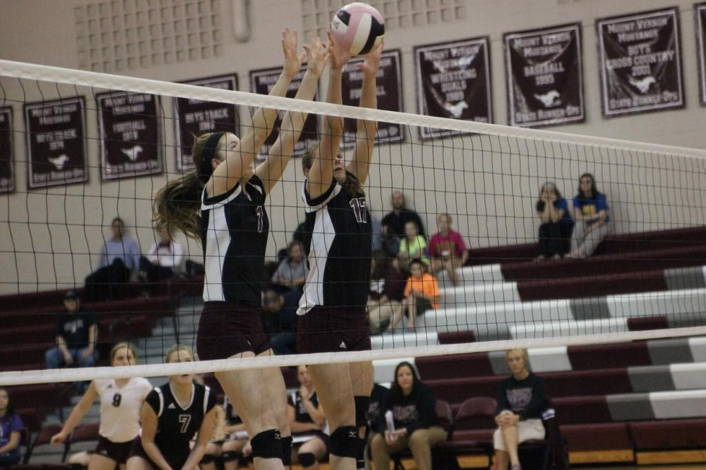 Mount Vernon's  Morgan Melchert (1) and number 17 Kaitlyn Volesky block an attack from Benton Community's middle hitter leading to a point for the Mustangs. Photo by Claire Pettinger.