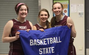 Abbey Teubel, Lexy Kroeger, and Alli Platte hold the state qulaifier banner after their 55-48 win over CPU Feb. 21.