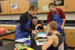 In biology class on Aug. 19, a group of sophomore boys laugh while conducting an experiment to study and practice the scientific method.