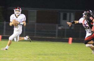 Quarterback Drew Adams looks for a receiver in the game against Monticello Sept. 25. Photo by Sam White.
