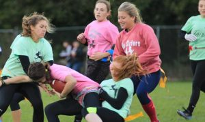 Junior Haley Corkin is stopped by sophomore Laurel Sherman and Senior Audrey Lester in the powderpuff game Oct. 1. Photo by Abdur Rafay.