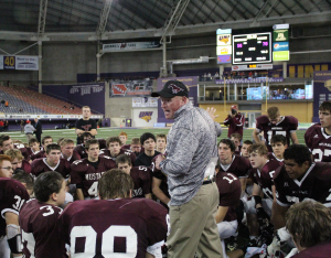 Head Coach Lance Pedersen talks to the team after the record-breaking state championship game Nov. 23. The photo tells the story of the hard fight with the high-scoring loss recorded on the scoreboard: Mount Vernon 56, Spirit Lake 70. Photo by Bailey Priborsky.