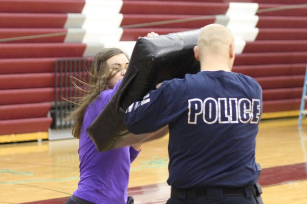 Senior Jenna Brannaman and officer Todd Gehrke show students how to defend themselves in Learning on a Dime, taught by Trista Lynner and Erin Wilkinson. Photo/Alex Moore.