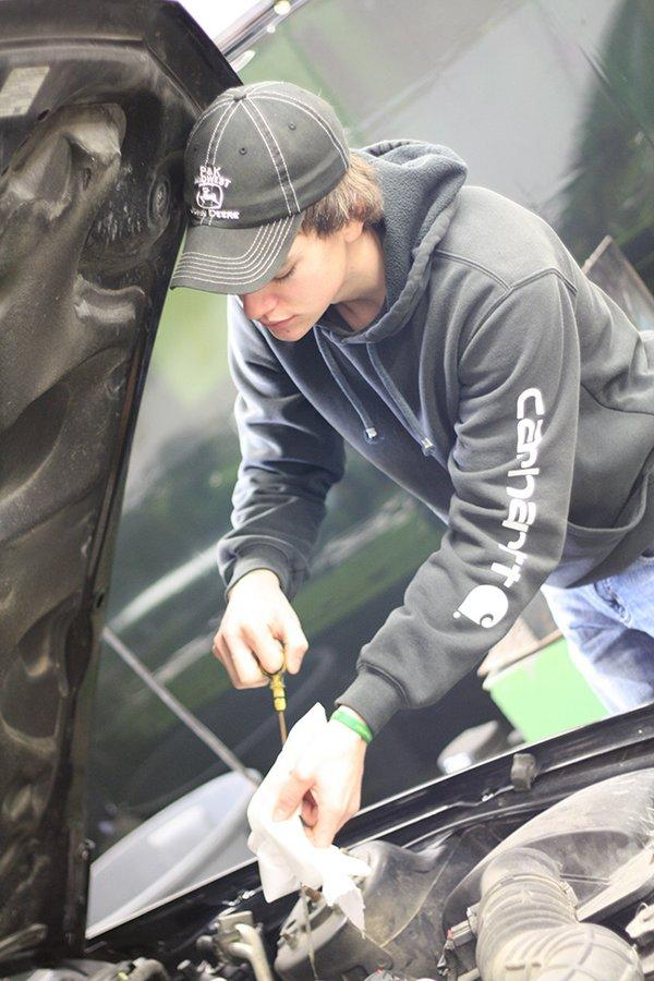 Noah Lineburg checks the oil in Consumer Automotive J-term. The class is offering services for vehicles to make money to do something fun together. Photo/Morgan Reilly .