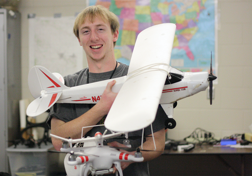 Jordan Axtell poses with a model airplane and a drone in science teacher Richard Scearce's class Jan. 7. Photo/ Mason Stanbro.