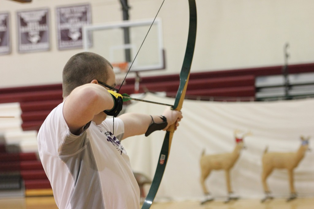 Junior Alex Moore takes a shot at a 3D deer Jan. 12 in Outdoor Pursuits, taught by German teacher and archery coach Tom Wilkinson. Photo/Zach Niehaus.