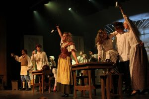 Raising a glass to all their accomplishments, the cast of Les Miserables celebrates during a dress rehearsal. Photo by Breanna Jones