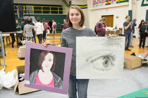 Kate Margheim holds her art entries.