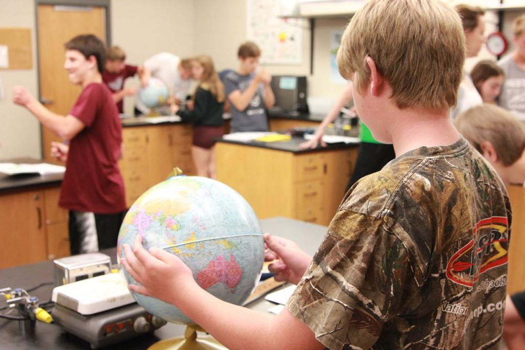 Freshman Logan Kelly performs an experiment in Earth Science class during the first block period of the year. Photo By Ben McGuire.