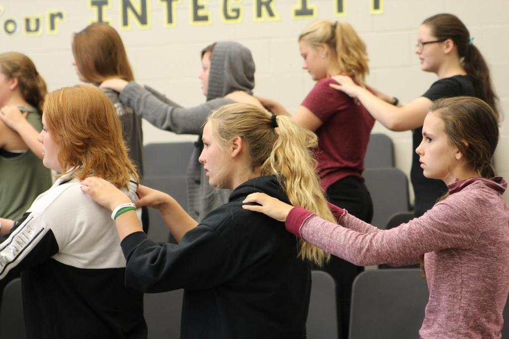 Members of the ninth and tenth grade women's choir warm up before class with massages. Photo by Lauren Hauser.