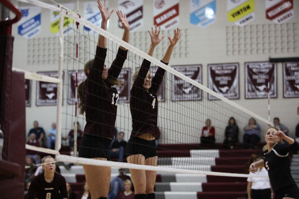 Kaitlyn Volesky and Rory Light work to block the ball at the front of the net during the volleyball playoff game.
