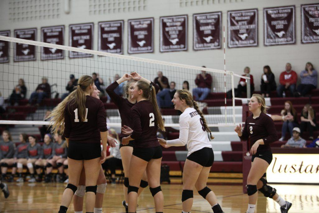 The volleyball team celebrates after scoring against Williamsburg.