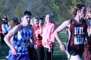 Seniors, Brittney Darrow and Wynne Vandersall, cheer on the team as Zach Krogmann runs by.