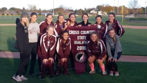 Girls XC team holds the banner after the qualifying meet at Solon on Oct. 20.