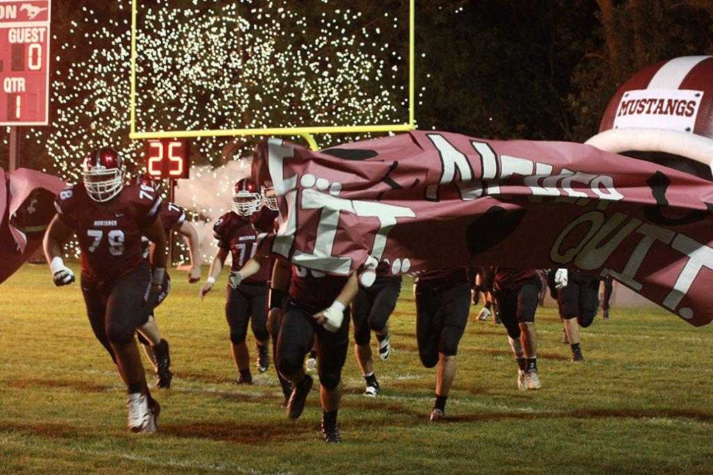 Before the game, football players break through the cheer banner as fireworks go off in the background. Photo by Emma Klinkhammer