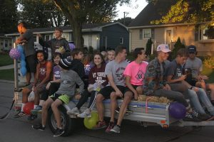 The cross country team rides a float in the homecoming parade Sept. 30. Photo by Lexi Flockhart.