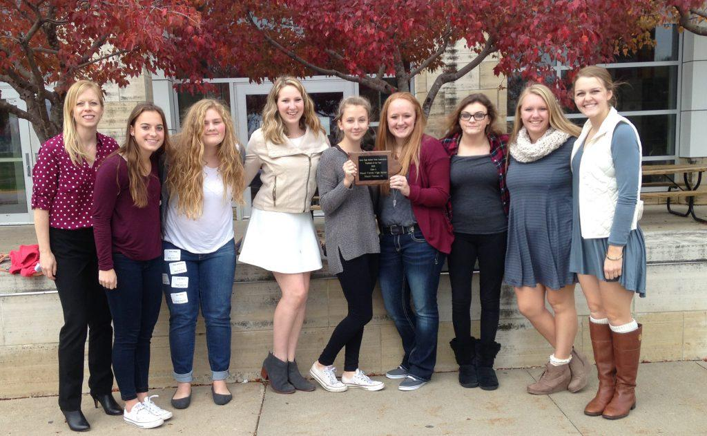 Returning yearbook staffers claimed the trophy at the conference Oct. 27. Adviser JoAnn Gage, Sydney Hauser, Emma Klinkhammer, Rachel Bell, Bailey Priborsky, Alyssa Maddocks, Abby Davidson, Jessie Brokel, and Kelsey Shady.