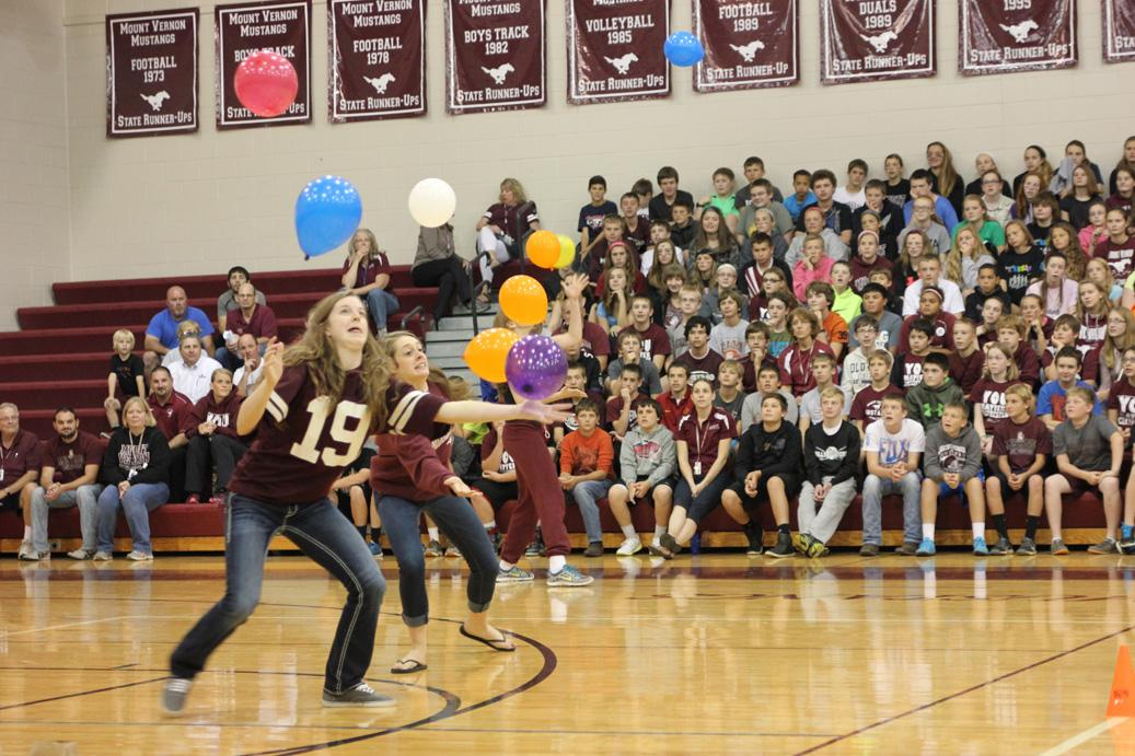 Volleyball players Morgan Melchert and Emma Cochrane attempt to keep balloons in the air at the All School Assembly Sept. 26. Photo by Gabby Zahradnik.