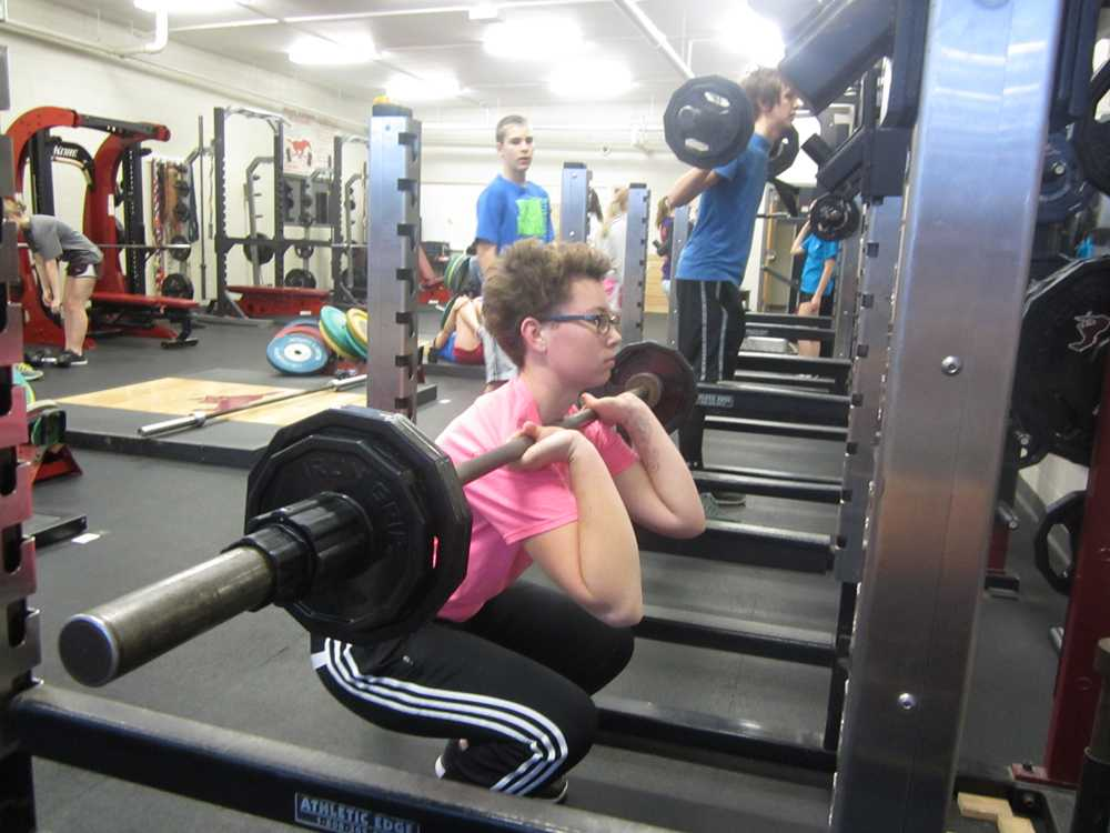 Senior Kate Elsbury lifts weights during earlybird P.E. on Dec. 11. Photo by Jenna Brannaman.
