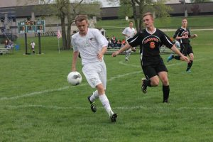 Sophomore Josh Trachta dribbles away from West Delaware's Sam Engelken May 4. The Mustangs beat the Hawks 4-1. Photo by Ethan Hill.