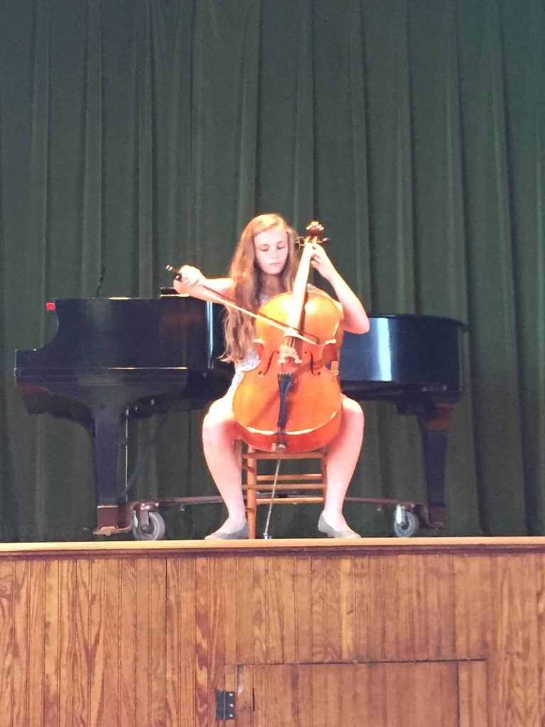 Clara Conroy plays cello on stage.