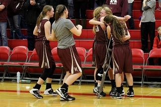 Teammates Catherine Yeoman, Delaney Dicus, Jacque Murray, Kaitlyn Volesky, and Riley Clark hug injured teammate Annie See after their regional final win against Solon (61-50) on Feb. 20.
