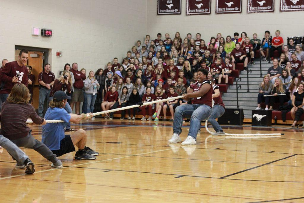 Senior Tristan Wirfs helps the football team win the first round of tug-of-war against the boys cross country team at the homecoming pep rally on Sept. 30. Photo by: Summer Everhart