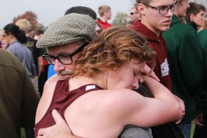 """Liam Conroy hugs his dad after the race. """"He's my inspiration, he taught me my work ethic. He's the one who told me I should go out for cross country, and I wouldn't be where I am without him,"""" Conroy said about his father. Photo by Ben McGuire."""