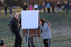 High school parent John Gruber-Miller and sophomore Sam White write messages in the middle of the circle.