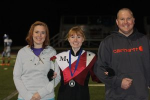 Mikayla Flockhart poses with her parents at senior night Oct. 14. Photo by Paige Zaruba.