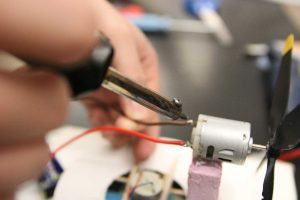 Senior Brandon Lochner fixing two wires during Science Olympiad on Feb 2nd.