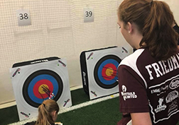 Senior Emily Friedman looks over at her shot at archery meet.