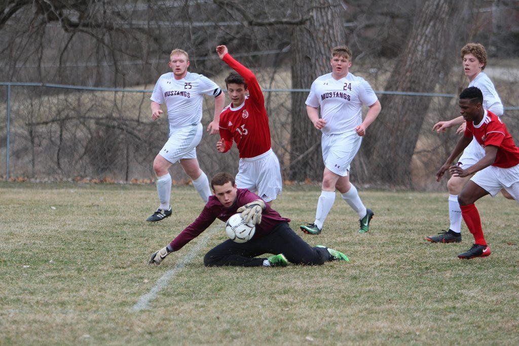 Goalie+Zach+Kolker+grabs+the+ball+away+from+a+Marion+player.+