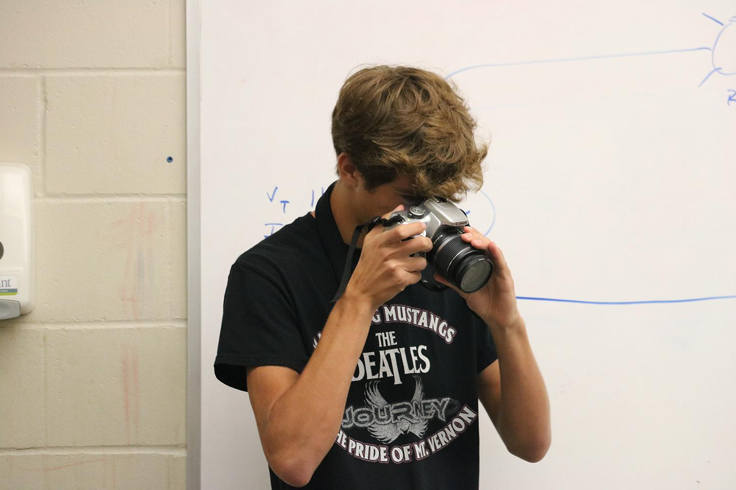 Junior Oliver Crocker takes photos of the electricity class on Aug. 31. Photo by Maddie Naeve.