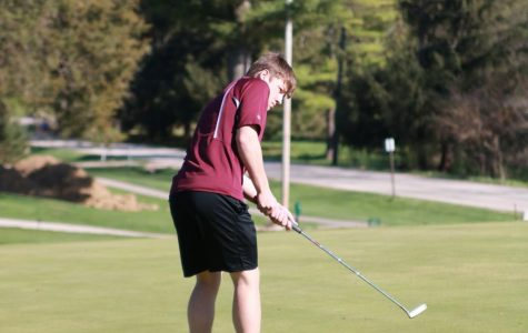 Sophomore Collin Swantz stands on the green and putts the ball in a meet against West Delaware.