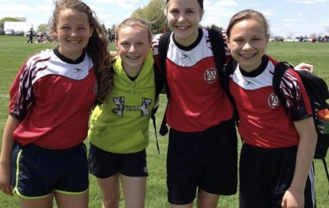 Seniors Alina Merlak, Sam White, Grace Krapfl, and Quinnie Rodman pose after an AYSO soccer game.