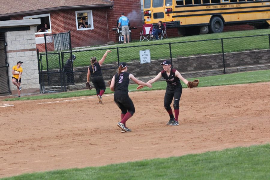 Sammy Moss, an incoming freshman at UNI, and Maia Bentley, incoming sophomore, clap hands during a softball game on May 24.