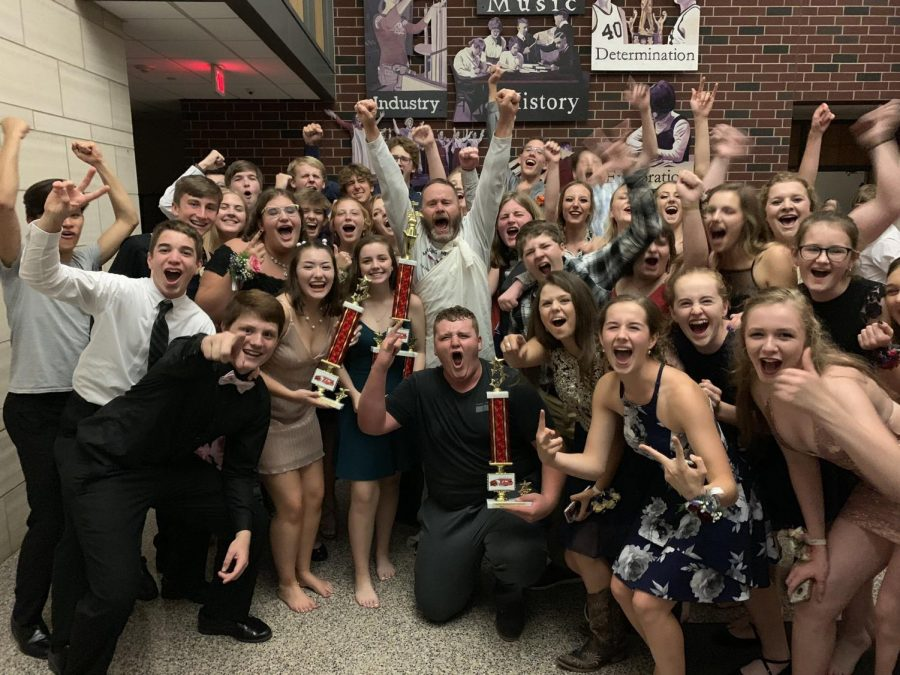 Marching Mustangs and director Scott Weber pose with trophies at the Homecoming dance.