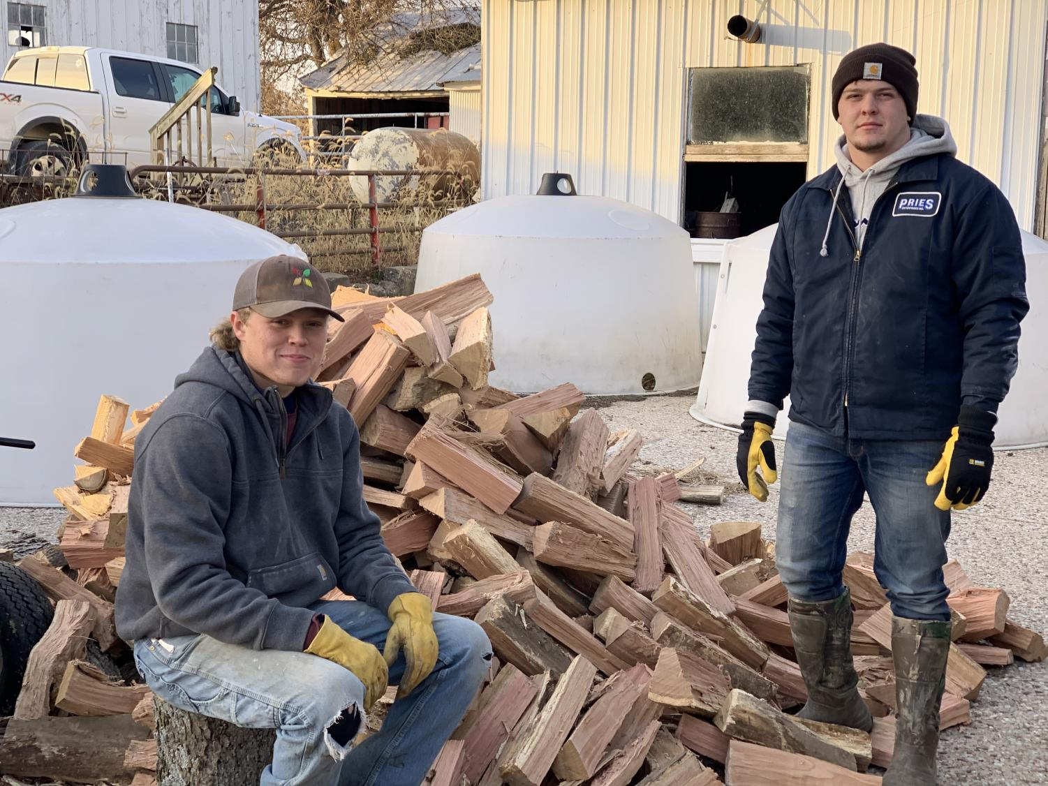 Trevor Ellison, junior, and Max Shady, senior, pose next to a pile of wood they  just cut.
