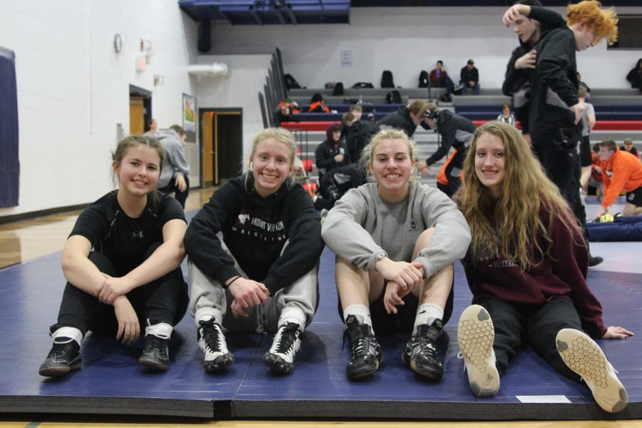 Wrestlers Abbie Morf, Julia Wheeler, Maddie Shultz, and Maddy Plotz pose at a tournament. Absent from photo are wrestlers Reagan Light and Tori Oelrich