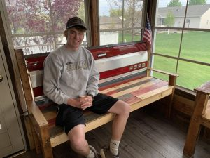 The Brand brothers made seven benches and sold five. Here Nolan poses with a bench he made that his family is keeping.
