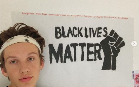 Dallas Olberding poses with his artwork in response to the killing of George Floyd May 25 and the protests of continued racial injustice.