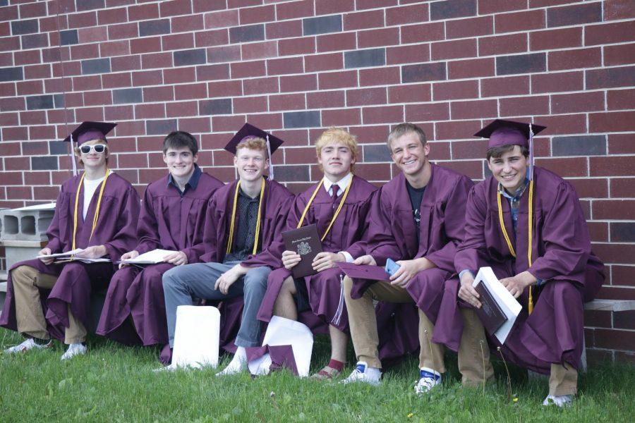 Luke Wade, Kode Banwart, Sam Adams, Graham Bradbury, Garrett Hormann, and Jack Kragenbrink sit behind the school after receiving their diplomas May 24.