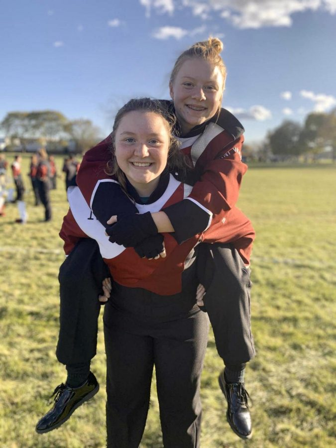 Jaegan Becthold holds her friend Lauren Swartzendruber while at a marching band competition in 2019.