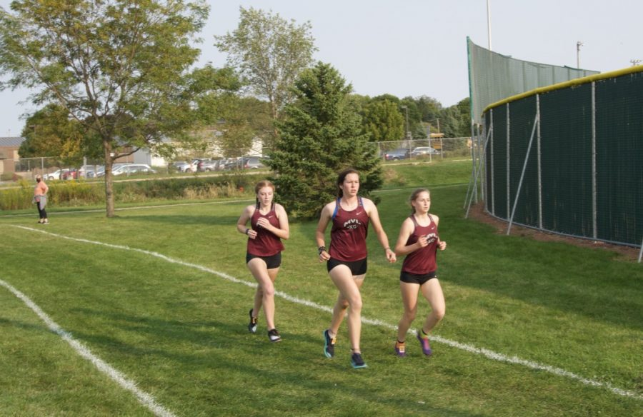 PACK RUNNING Sophomore Laila Moellering (22:32), Junior Nadia Telecky (22:19), and Senior Sabrina Bleile (22:22) stay together as they race toward the finish.