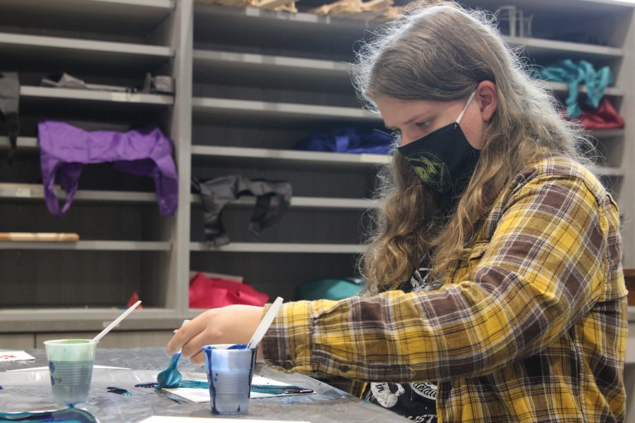 Senior Quinn Alles pours paint onto a canvas in Art Media Survey Sept. 11. Alles used three different colors in her acrylic pour painting.